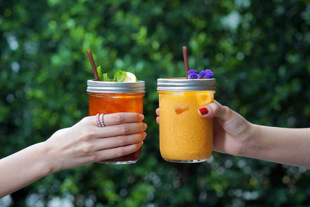 How to Cold Brew Tea—Image shows two hands holding a jar of iced tea and a jar of juice together—cheers!