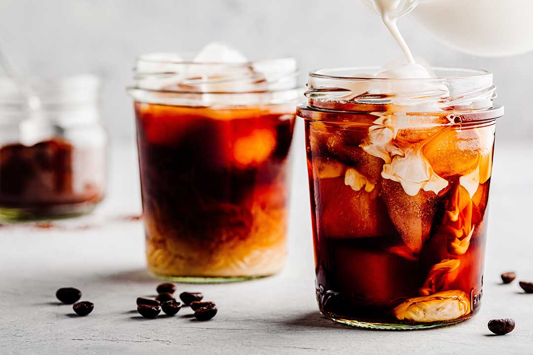 How to Cold Brew Tea—Image shows glasses of milk tea on a white, wooden surface