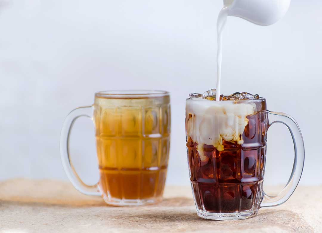 How to Cold Brew tea—Image shows a cup of green tea and a cup of black tea with milk being poured into it.