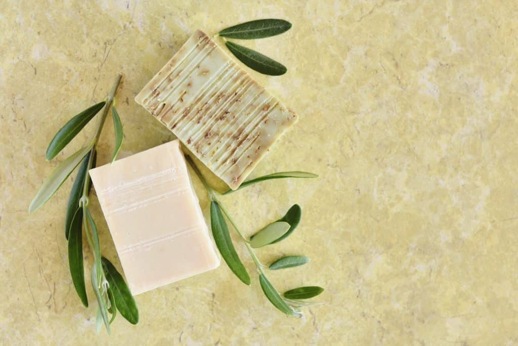 Handmade soap bars and olive branches on color background, top view. (Soap Making Kits for Beginners)