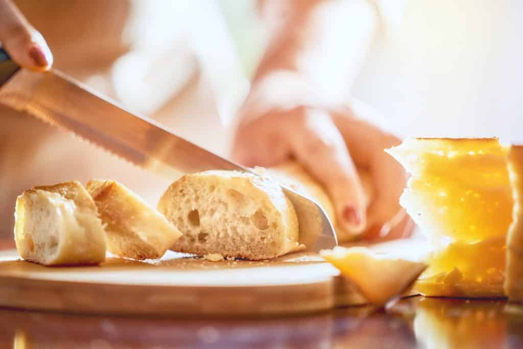 Flour, water, salt, and yeast—it's not quite as easy as it sounds! We'll help you make your first loaf of bread with these bread baking tips for beginners. (Hands of person cutting bread and cheese on wooden table.)