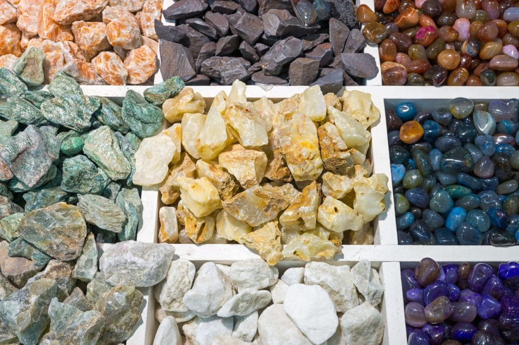 Rock collecting is one of a few hobbies that has the potential to be both rewarding and profitable. Learn more in our rock collecting for beginners guide! (Image shows boxes of colourful semi-precious stones)
