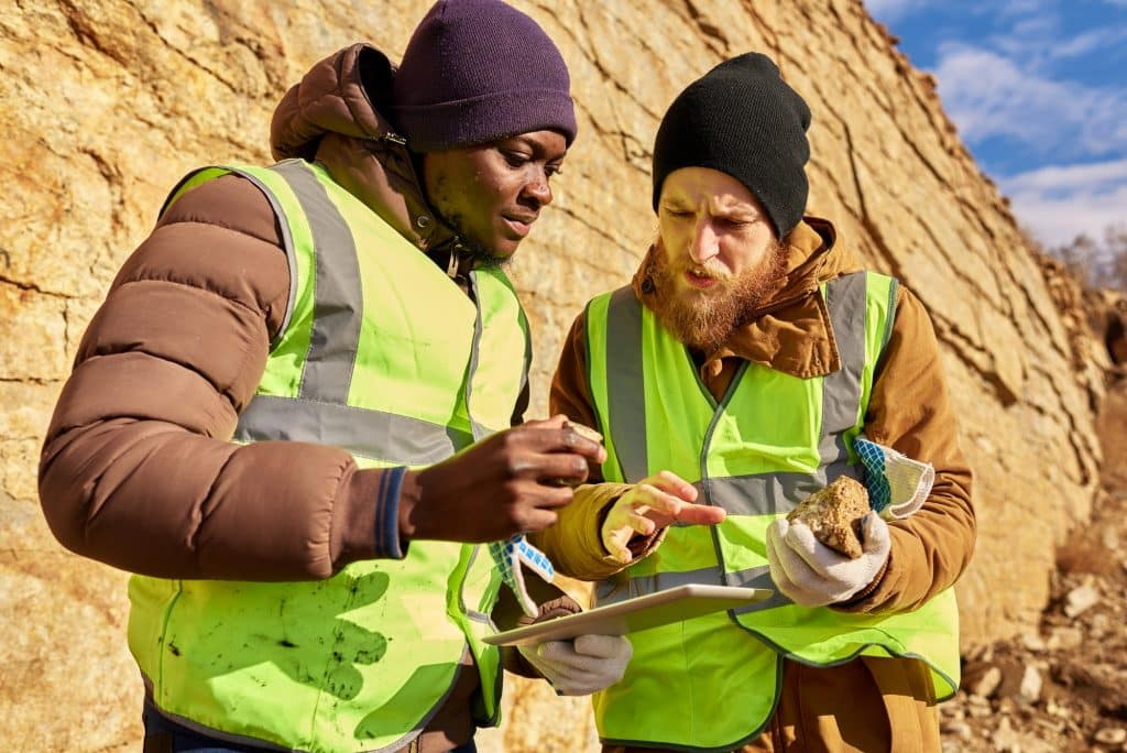 Rock collecting is one of a few hobbies that has the potential to be both rewarding and profitable. Learn more in our rock collecting for beginners guide! (Image shows diggers Inspecting worksite searching for minerals)