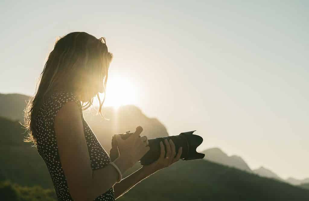 Image shows a woman looking at her DSLR camera with the sunrise in the background.
