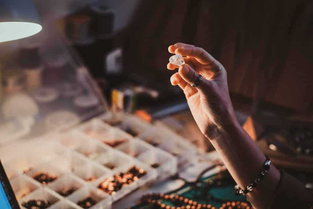 Learn how to make your own tumbled stone jewelry to wear, give as gifts, or sell at your local market days. Here are all the tools you need to get started! (Image shows a girl holding semi precious stone.)