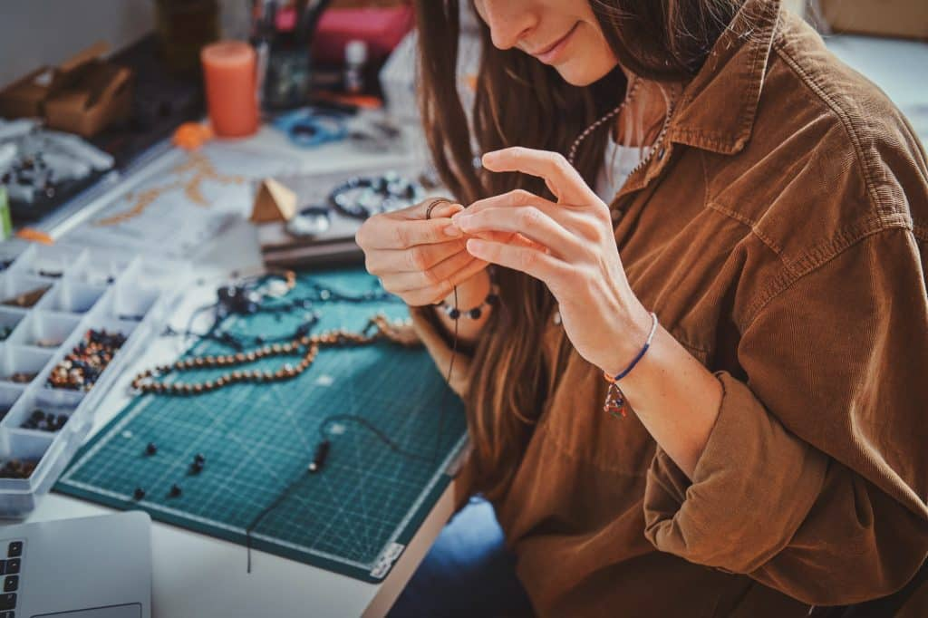 Learn how to make your own tumbled stone jewelry to wear, give as gifts, or sell at your local market days. Here are all the tools you need to get started! (Image shows a girl making new beaded jewelry.)