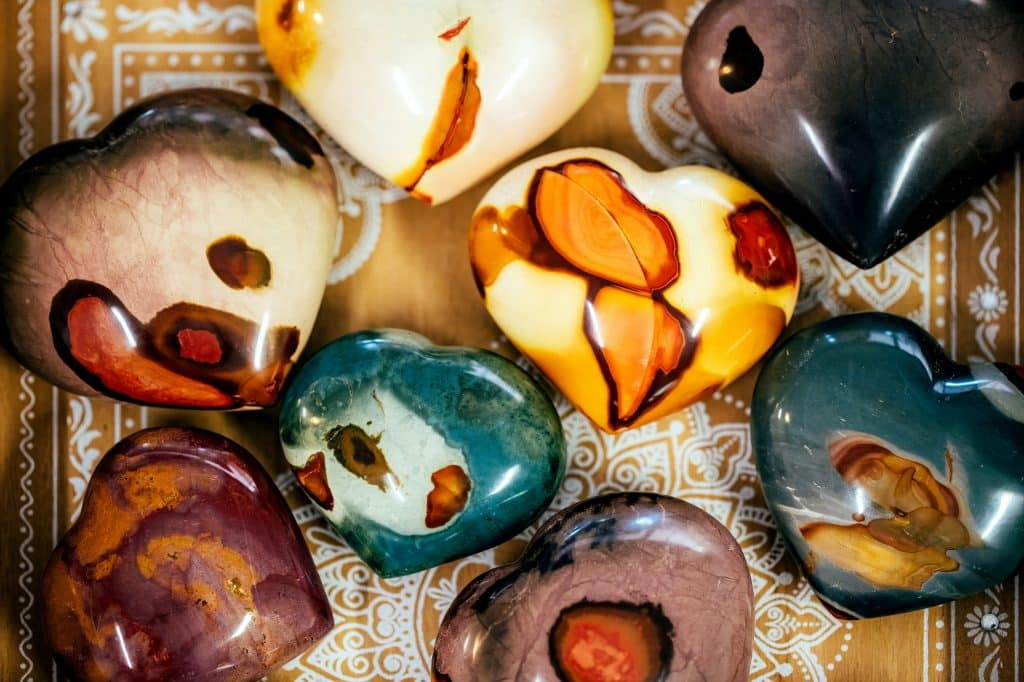 Learn how to make your own tumbled stone jewelry to wear, give as gifts, or sell at your local market days. Here are all the tools you need to get started! (Image shows various stones, minerals, gems on a yellow background.)