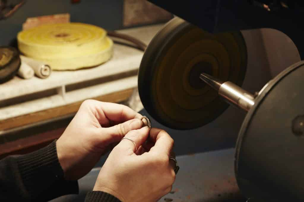 A person holding a small ring and using a grinding machine to shape and polish it. Workbench in a