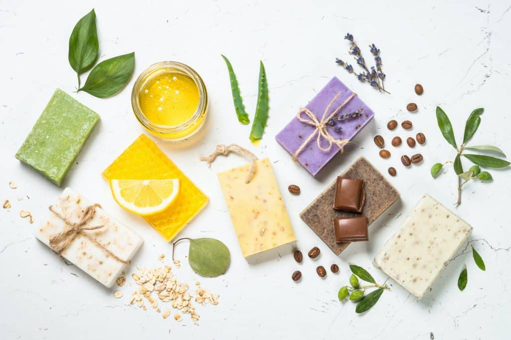 Looking for the best melt and pour soap base to supplement products or to give as gifts for friends and family? Check out some of our favorites! (Image shows assorted natural soap bars on a white  background, top view)