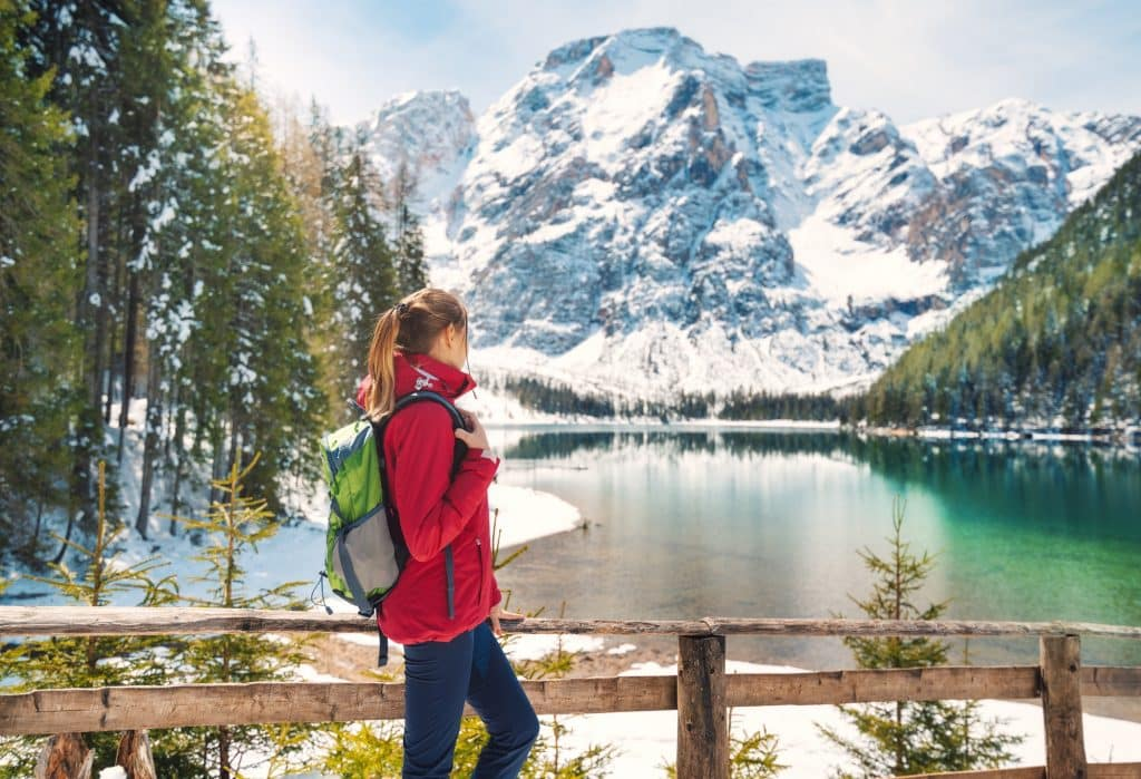 Young woman with backpack near wooden fence and Braies lake