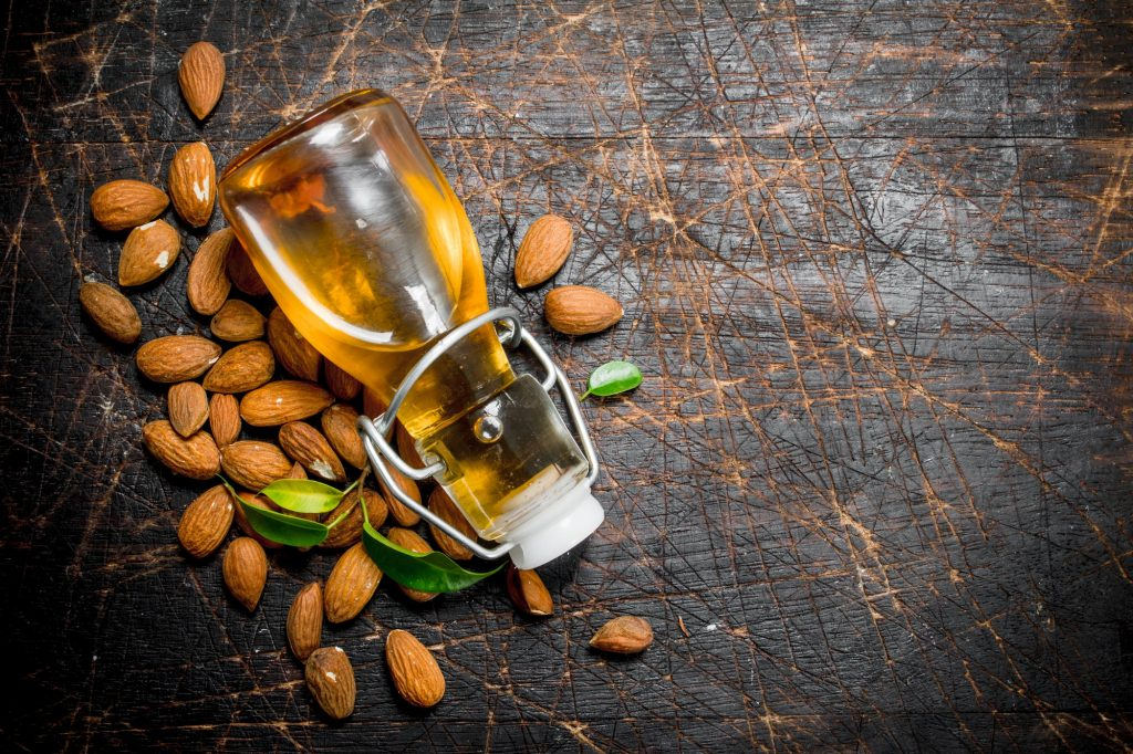 Bottle of almond oil on a dark wooden surface, surrounded by almonds.