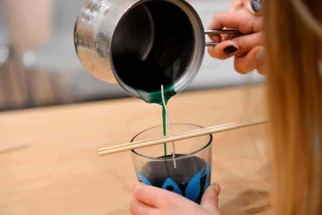 Image shows a girl making a candle, pouring blue wax into a glass, with a wick held in the center by two wooden sticks.