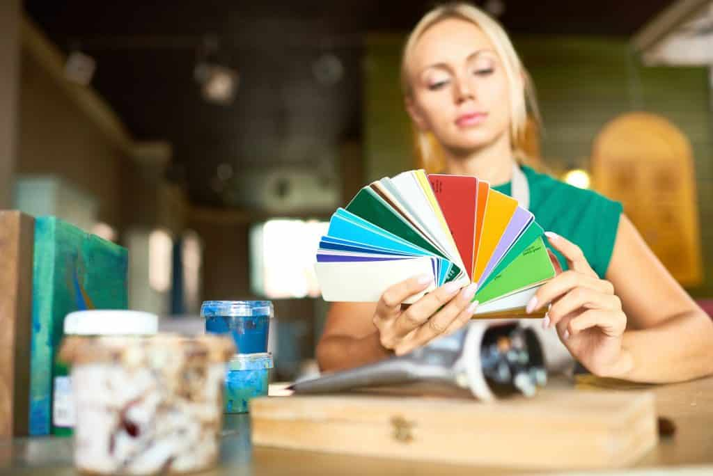 Interior design can make for a relaxing hobby and an organized space. Here's how interior design affects mental health. Image shows a designer choosing colors for interior.