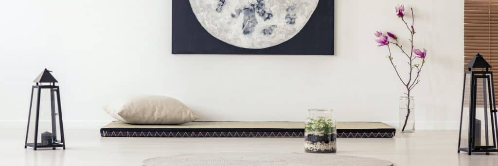 Moon poster above futon in Japanese bedroom interior with flower